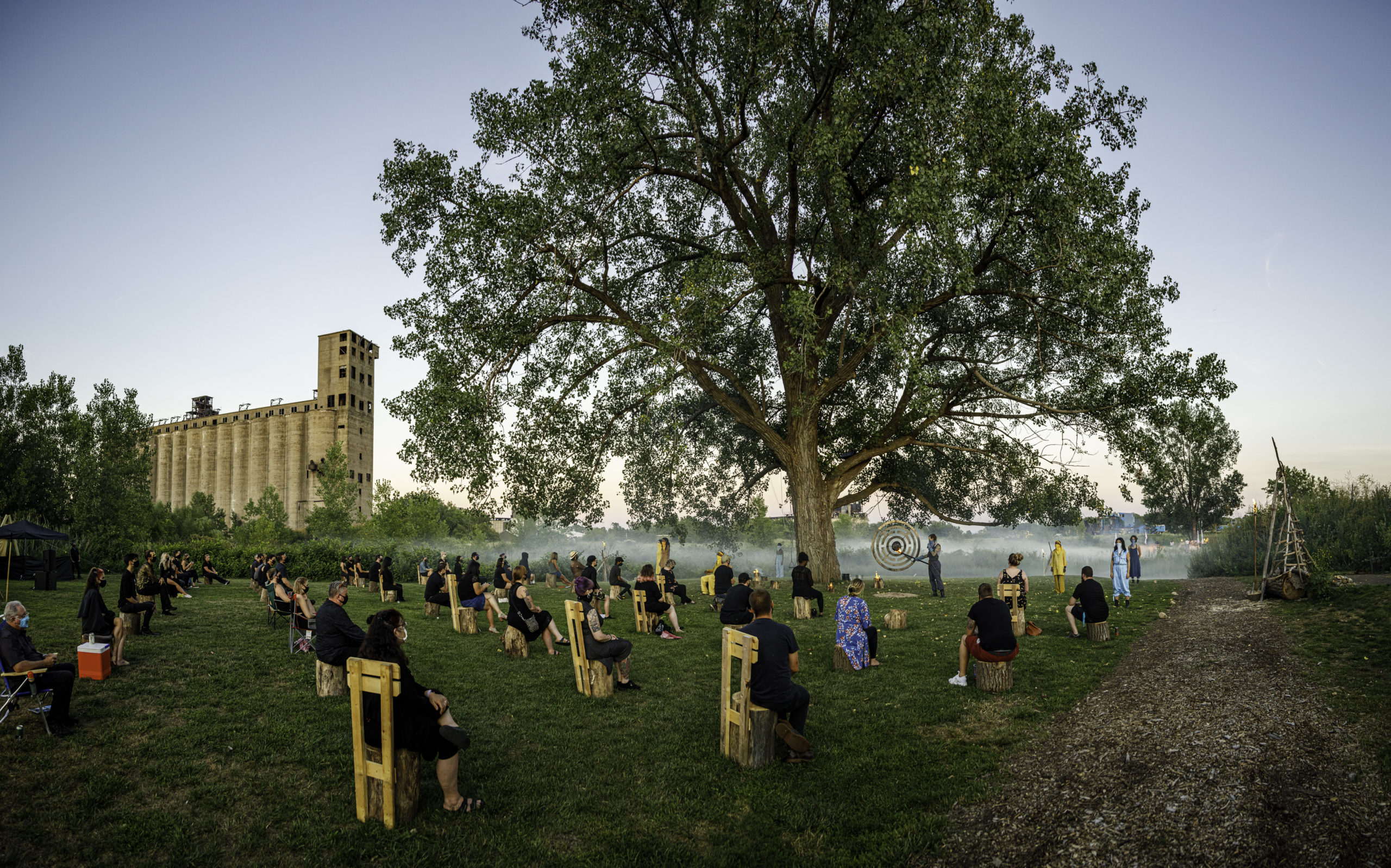 Photograph of a large tree in a grassy field with smoke blanketing the ground like mist, in the background the large imposing concrete grain elevator, with individual audience members seated in wooden chairs, each distanced from one another, around the tree.